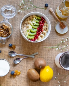 Food Photography Portfolio at ildiva.com - Breakfast table flat lay with Oatmeal Bowl, Fruit, Walnuts, Honey, Milk and Coffee
